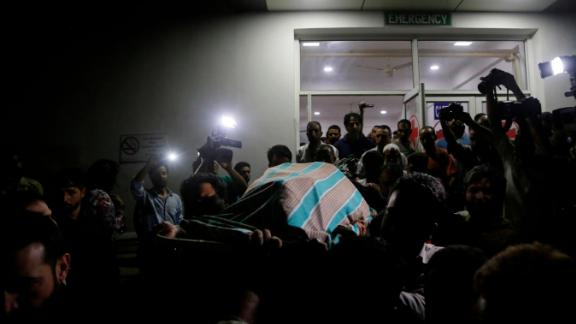 Friends and relatives carry out the body of journalist Shujaat Bukhari from a police control room in Srinagar, India, Thursday.