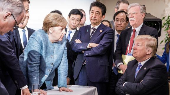 CHARLEVOIX, CANADA - JUNE 9:   In this photo provided by the German Government Press Office (BPA), German Chancellor Angela Merkel deliberates with US president Donald Trump on the sidelines of the official agenda on the second day of the G7 summit on June 9, 2018 in Charlevoix, Canada. Also pictured are (L-R) Larry Kudlow, director of the US National Economic Council, Theresa May, UK prime minister, Emmanuel Macron, French president, Angela Merkel, Yasutoshi Nishimura, Japanese deputy chief cabinet secretary, Shinzo Abe, Japan prime minister, Kazuyuki Yamazaki, Japanese senior deputy minister for foreign affairs, John Bolton, US national security adviser, and Donald Trump. Canada are hosting the leaders of the UK, Italy, the US, France, Germany and Japan for the two day summit. (Photo by Jesco Denzel /Bundesregierung via Getty Images)