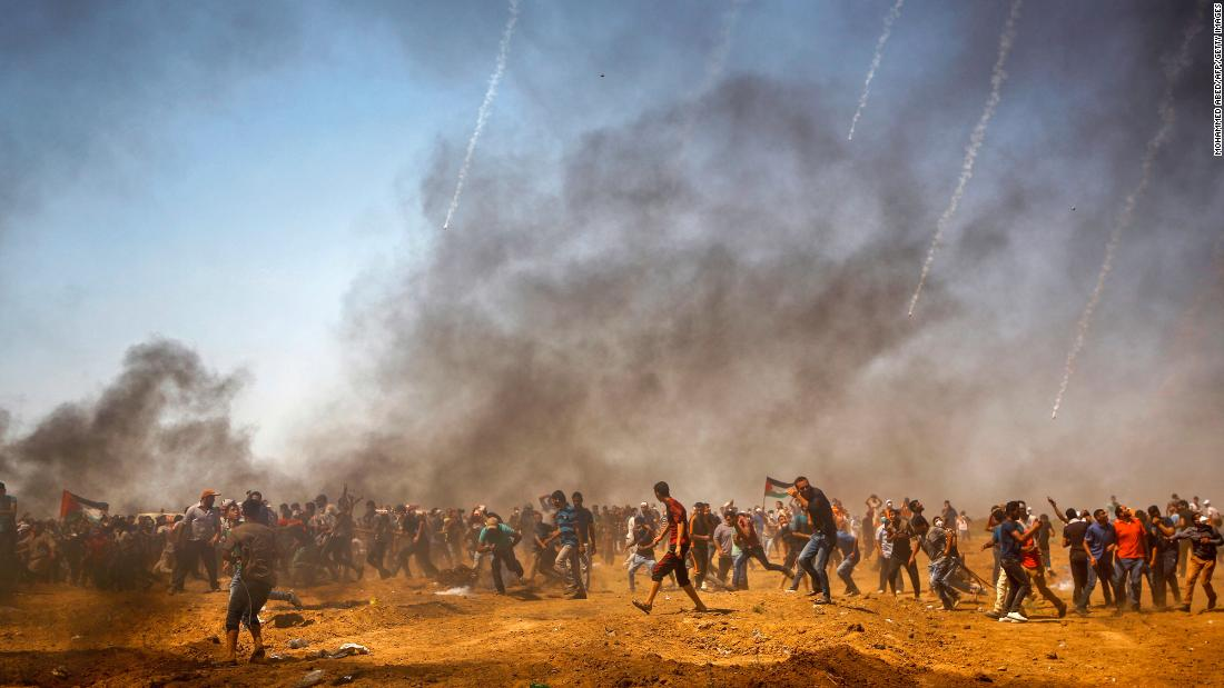 "Palestinian protesters take cover from tear gas as <a href=""https://www.cnn.com/2018/06/08/middleeast/israel-forces-kill-palestinians-in-gaza/index.html"" target=""_blank"">they demonstrate along the Gaza-Israel border</a> on Friday, June 8."