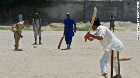 Afghan refugees play a cricket match at the Khurasan refugee camp in the suburbs of Peshawar on July 6, 2017.