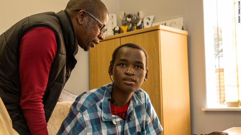 Mzwandile Khumalo, an MSF field coordinator, tests Khumbulani Shandu's new cochlear implant.