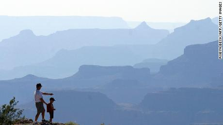 A father and son look out over the South Rim of the Grand Canyon, a detour off historic Route 66, in Arizona, 10 July 2003. More than four million people visit the Grand Canyon every year, most arriving by car. AFP PHOTO / Robyn BECK (Photo credit should read ROBYN BECK/AFP/Getty Images)