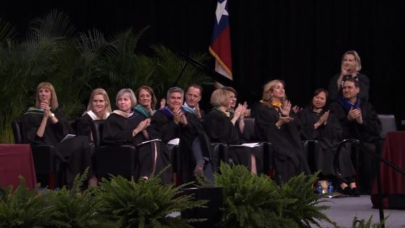Faculty members applaud as Scott gives his speech.