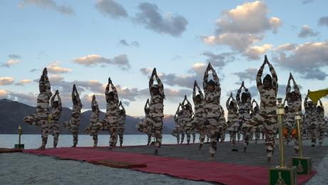 Members of the Indo-Tibetan Border Police practice tree pose during a yoga class in the Himalayan mountains.