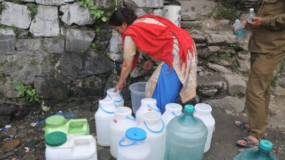 Indian residents wait to collect drinking water in Shimla as the city faces water shortage.