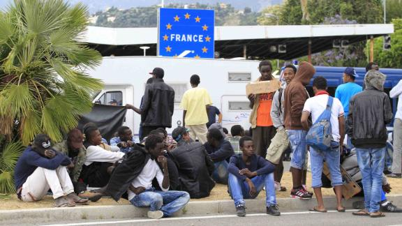 Migrants wait at the border between Italy and France in the city of Ventimiglia on June, 12, 2015. The Schengen open borders accord means migrants landing in Italy can usually easily travel through neighbouring France, Austria, Switzerland and Slovenia as they seek to make it to Britain, Germany and Scandinavia, but the G7 suspension of Schengen and a growing number of spot checks on buses and trains has made that harder, increasing the pressure on Italy, where reception facilities are at breaking point with some 76,000 people being accommodated nationwide. AFP PHOTO / JEAN-CHRISTOPHE MAGNENET        (Photo credit should read JEAN-CHRISTOPHE MAGNENET/AFP/Getty Images)