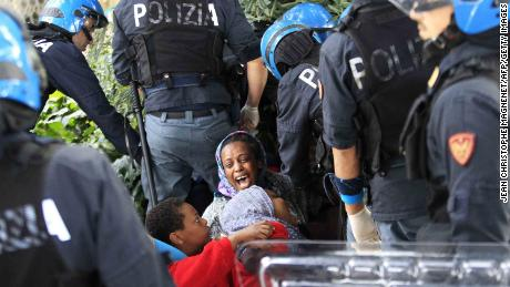 Italian police officers surround a family of migrants during an operation to remove them from the Italian-French border in the Italian city of Ventimiglia on June, 16, 2015.