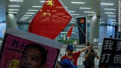 A Pro-Beijing protester (back centre) holds a Chinese flag during the anti-rail link rally outside the Legco complex in Hong Kong on June 14.