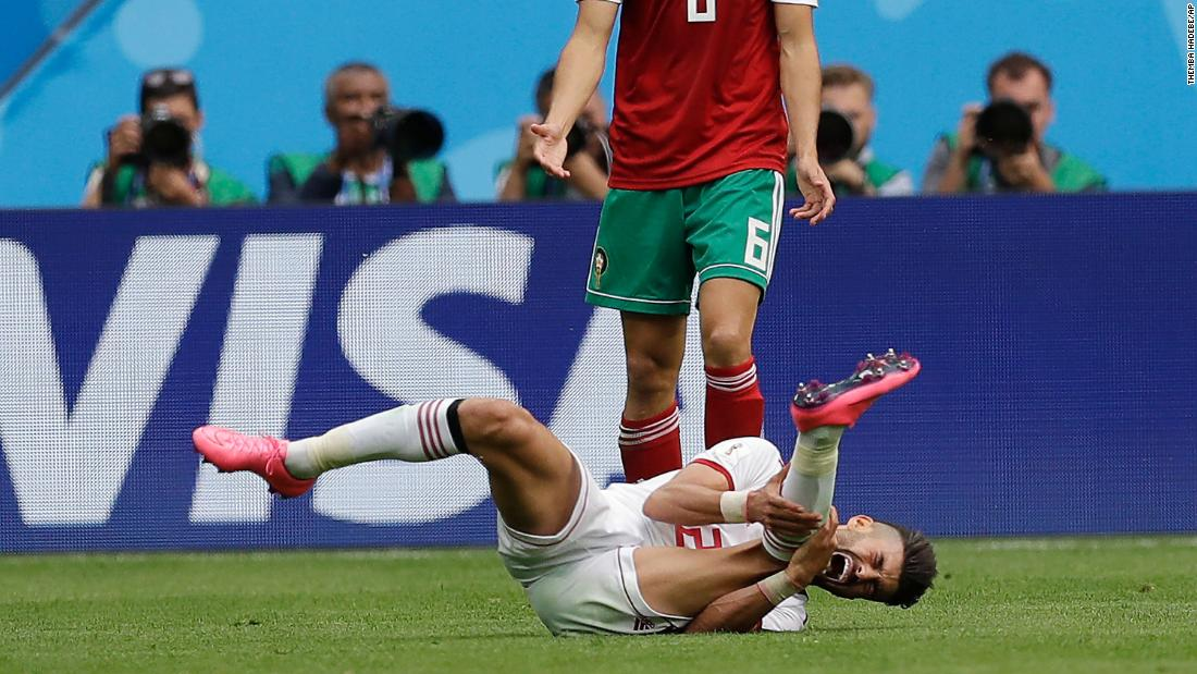 Iran's Alireza Jahanbakhsh grimaces in pain in front of Morocco's Romain Saiss.