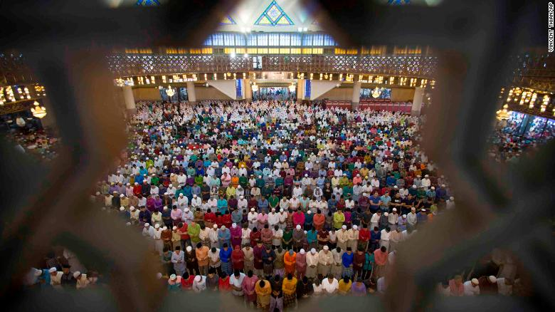 Malaysian Muslims offer prayers during the first day of Eid al-Fitr, which marks the end of the holy fasting month of Ramadan in Kuala Lumpur, Malaysia, Friday, June 15, 2018. (AP Photo/Vincent Thian)