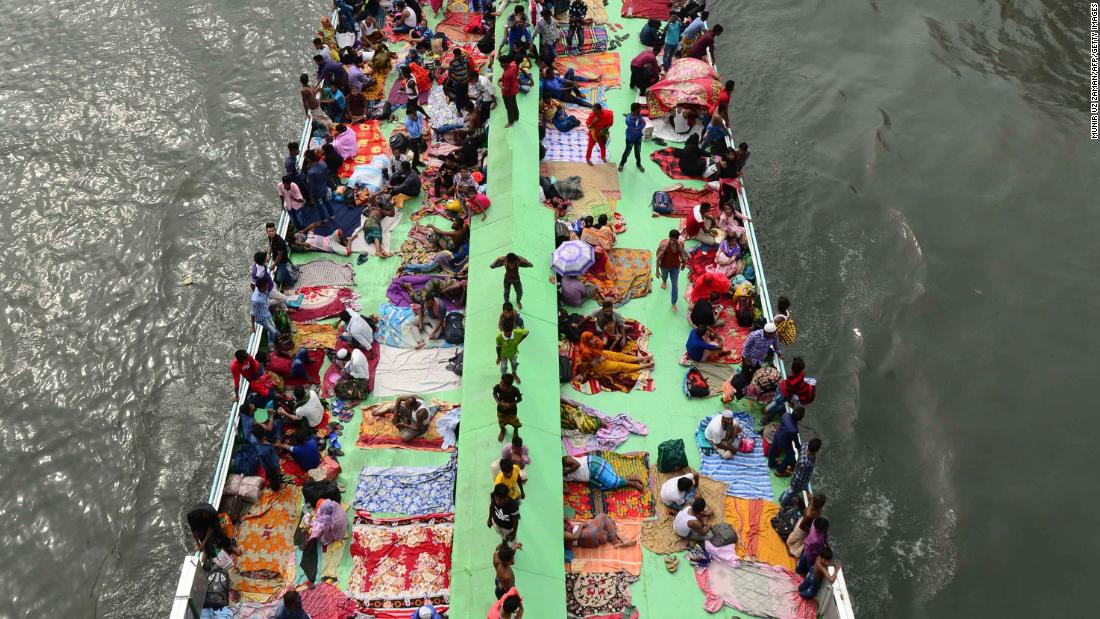 People travel on a ferry along the Buriganga River, on the outskirts of Dhaka, Bangladesh, to be with their families for Eid.