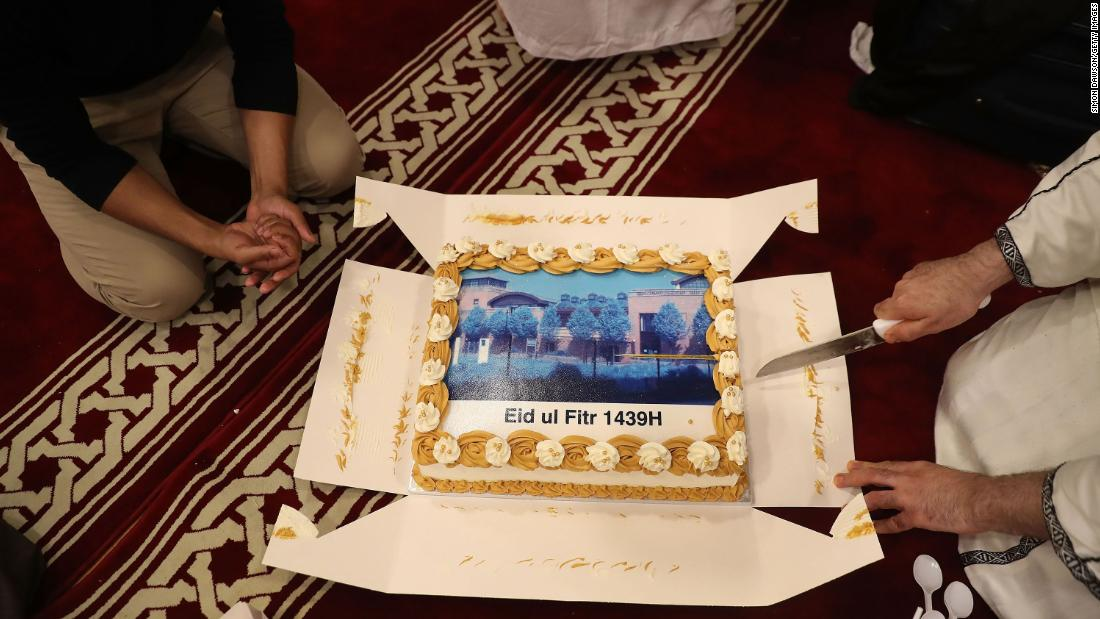 Worshippers at the Al Manaar mosque in London cut a cake to celebrate Eid.