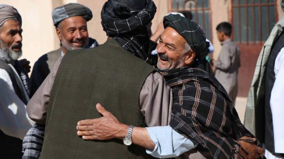 People greet each other after offering prayers in Herat, Afghanistan.