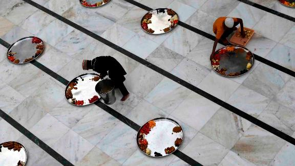Boys serve food on trays as people prepare to break their fast at the Minara Masjid mosque in Mumbai, India.