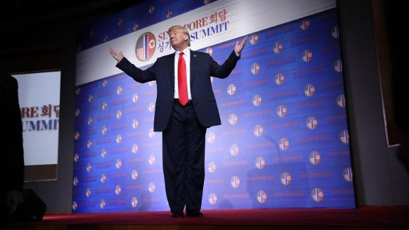 """SINGAPORE - JUNE 12:  U.S. President Donald Trump answers a final question while departing a press conference following his historic meeting with North Korean leader Kim Jong-un June 12, 2018 in Singapore. Trump described his meeting with Kim as """"better than anyone could have expected.""""  (Win McNamee/Getty Images)"""