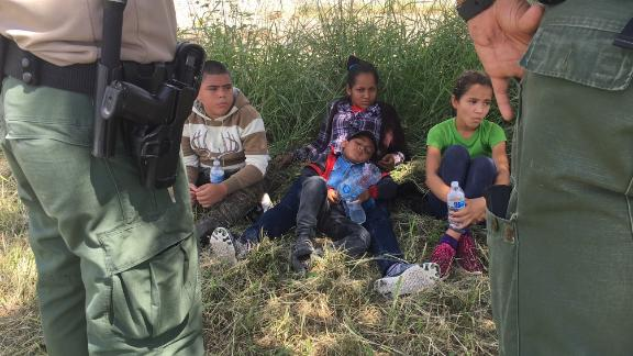 Dalila Suyapa and her son Cesar (center) take a break from the sun after Border Patrol agents took them in custody in Mission, Texas on June 16, 2018.