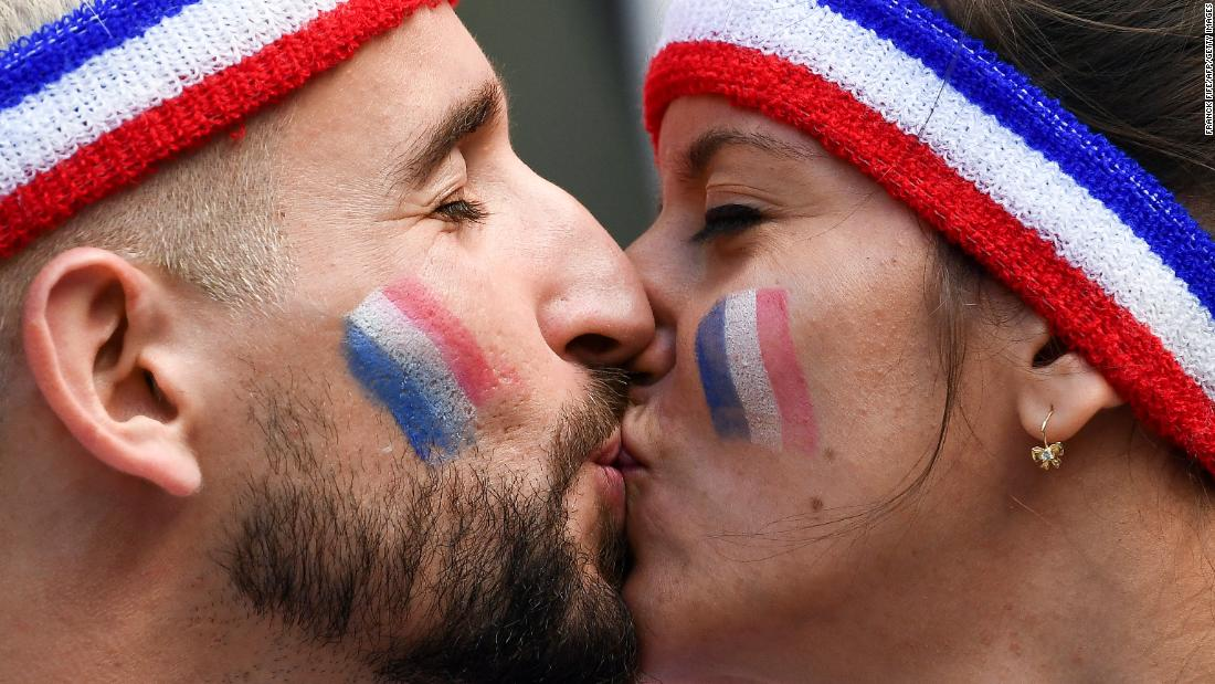Fans of France share a kiss before the team's opening match with Australia.