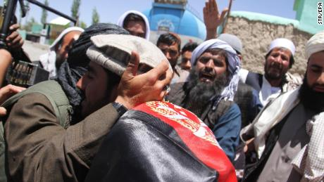 Purported Taliban militants and Afghans embrace Saturday in Ghazni during a three-day truce for Eid.