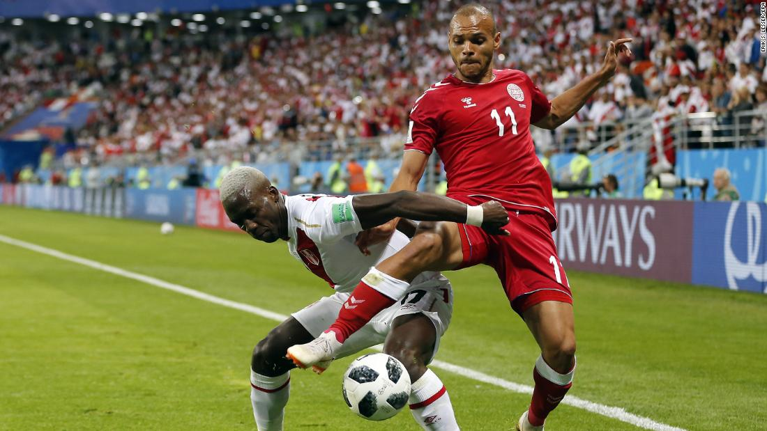 Peru's Luis Advincula, left, and Denmark's Martin Braithwaite fight for the ball.