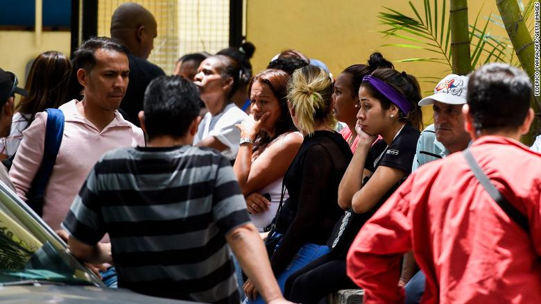 "Relatives of the victims of the night club ""Los Cotorros"" -where a tear gas grenade was detonated earlier today- wait outside the morgue in Caracas on June 16, 2018. - Seventeen people, including eight minors, were killed after a brawl broke out during a middle school graduation party and someone detonated the tear gas, sending more than 500 people rushing for the exits (Photo by Federico PARRA / AFP)        (Photo credit should read FEDERICO PARRA/AFP/Getty Images)"