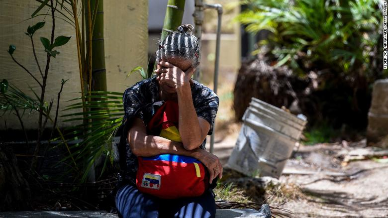 "A relative of one of the victims of the night club ""Los Cotorros"" -where a tear gas grenade was detonated- waits outside the morgue in Caracas on June 16, 2018. - Seventeen people, including eight minors, were killed after a brawl broke out during a middle school graduation party and someone detonated the tear gas, sending more than 500 people rushing for the exits (Photo by Federico PARRA / AFP)        (Photo credit should read FEDERICO PARRA/AFP/Getty Images)"