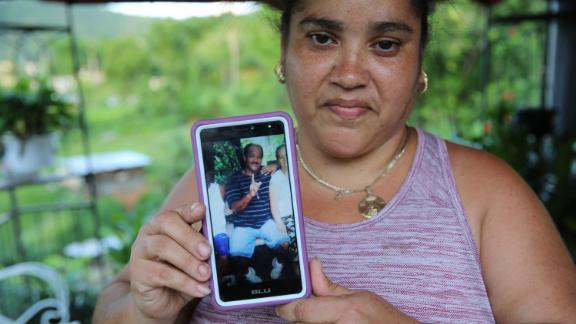 "Lisa De Jesús holds a picture of her deceased friend, ""Rey Bruquena,"" or ""Rey Crab,"" who earned that nickname because of his love for the ocean."