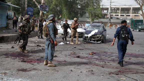 Afghan security officials inspect the scene of Sunday's suicide bombing near a meeting between the Nangarhar governor and Taliban militants.