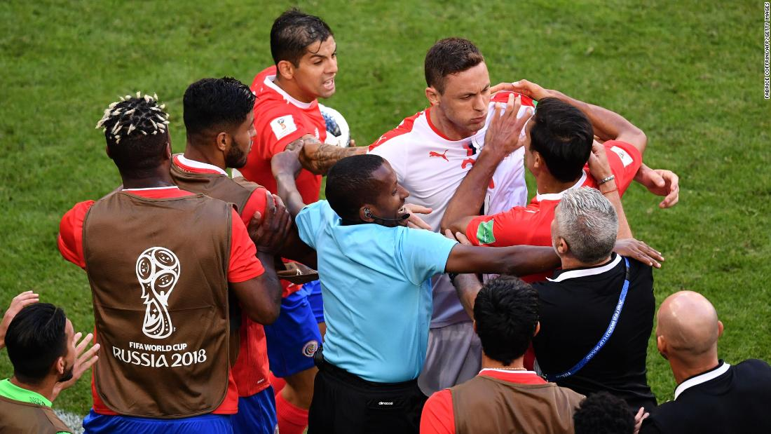 Serbian midfielder Nemanja Matic, center right, is held back by Costa Rican players following an altercation with one of their coaches.