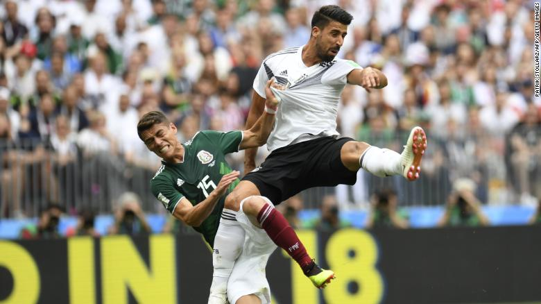 TOPSHOT - Germany's midfielder Sami Khedira (R) and Mexico's defender Hector Moreno (L) fall after attempting to head the ball during the Russia 2018 World Cup Group F football match between Germany and Mexico at the Luzhniki Stadium in Moscow on June 17, 2018. (Photo by Patrik STOLLARZ / AFP) / RESTRICTED TO EDITORIAL USE - NO MOBILE PUSH ALERTS/DOWNLOADS        (Photo credit should read PATRIK STOLLARZ/AFP/Getty Images)