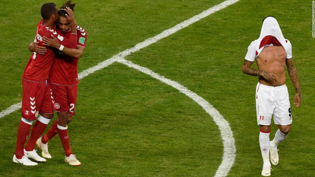 Peru΄s forward Paolo Guerrero walks with his shirt over his face as two members of Denmark΄s team celebrate after the football match between Peru and Denmark on Saturday, June 16. Denmark defeated Peru 1-0.