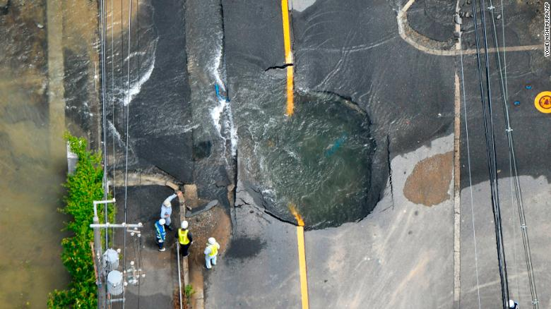 Water floods out from crack in the road, following the Osaka quake.