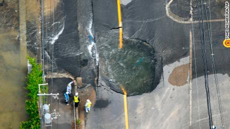 Water floods out from crack in the road, following an earthquake in Takatsuki, Osaka, Monday, June 18, 2018. A strong earthquake knocked over walls and set off scattered fires around the city of Osaka in western Japan on Monday morning.(Yohei/Nishimura /Kyodo News via AP)