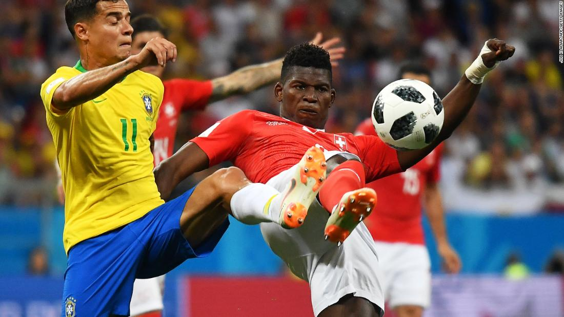 Brazil's Philippe Coutinho and Switzerland's Breel Embolo compete for the ball.