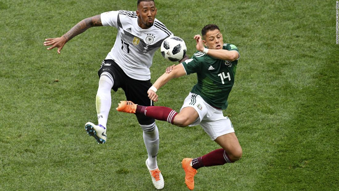 Germany's Jerome Boateng vies for the ball with Mexico's Javier Hernandez.