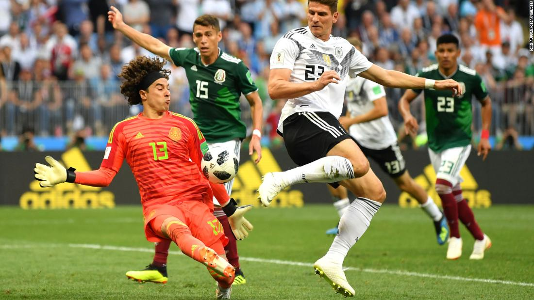 Mexican goalkeeper Guillermo Ochoa makes a late save against Mario Gomez.