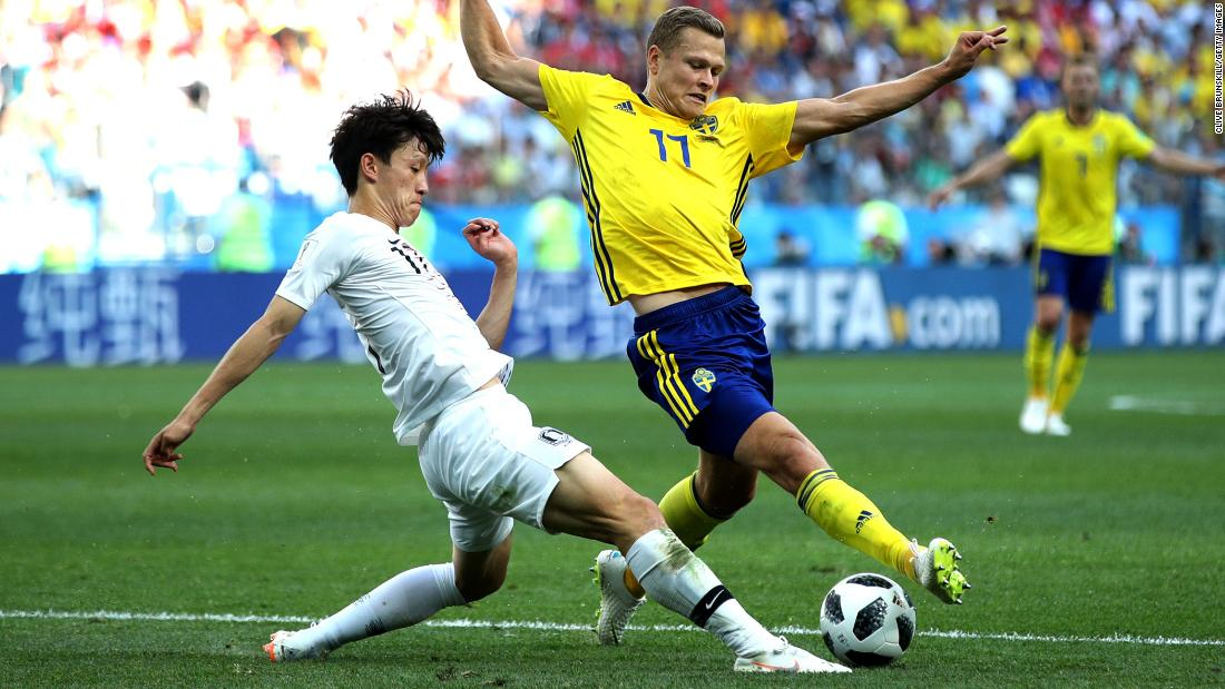 Viktor Claesson of Sweden is tackled by Lee Jae-sung of South Korea.