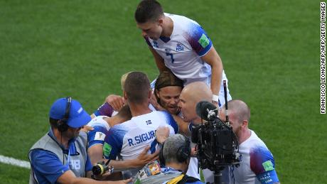Iceland's forward Alfred Finnbogason (hidden) is congratulated by teammates after scoring against Argentina.