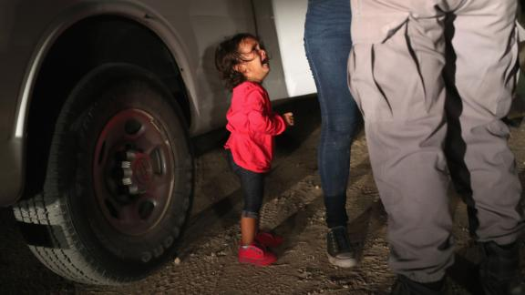 MCALLEN, TX - JUNE 12:  A two-year-old Honduran asylum seeker cries as her mother is searched and detained near the U.S.-Mexico border on June 12, 2018 in McAllen, Texas. The asylum seekers had rafted across the Rio Grande from Mexico and were detained by U.S. Border Patrol agents before being sent to a processing center for possible separation. Customs and Border Protection (CBP) is executing the Trump administration