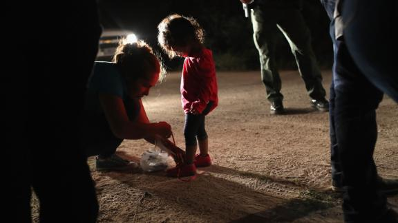 "MCALLEN, TX - JUNE 12:  A Honduran mother removes her two-year-old daughter's shoe laces, as required by U.S. Border Patrol agents, after being detained near the U.S.-Mexico border on June 12, 2018 in McAllen, Texas. The asylum seekers had rafted across the Rio Grande from Mexico and were detained by federal authorities before being sent to a processing center for possible separation. Customs and Border Protection (CBP) is executing the Trump administration's ""zero tolerance"" policy towards undocumented immigrants. U.S. Attorney General Jeff Sessions also said that domestic and gang violence in immigrants' country of origin would no longer qualify them for political asylum status.  (Photo by John Moore/Getty Images)"