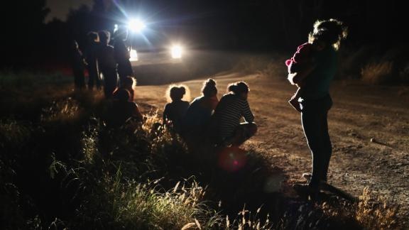 """MCALLEN, TX - JUNE 12:  U.S. Border Patrol agents arrive to detain a group of Central American asylum seekers near the U.S.-Mexico border on June 12, 2018 in McAllen, Texas. The group of women and children had rafted across the Rio Grande from Mexico and were detained before being sent to a processing center for possible separation. Customs and Border Protection (CBP) is executing the Trump administration's """"zero tolerance"""" policy towards undocumented immigrants. U.S. Attorney General Jeff Sessions also said that domestic and gang violence in immigrants' country of origin would no longer qualify them for political asylum status.  (Photo by John Moore/Getty Images)"""