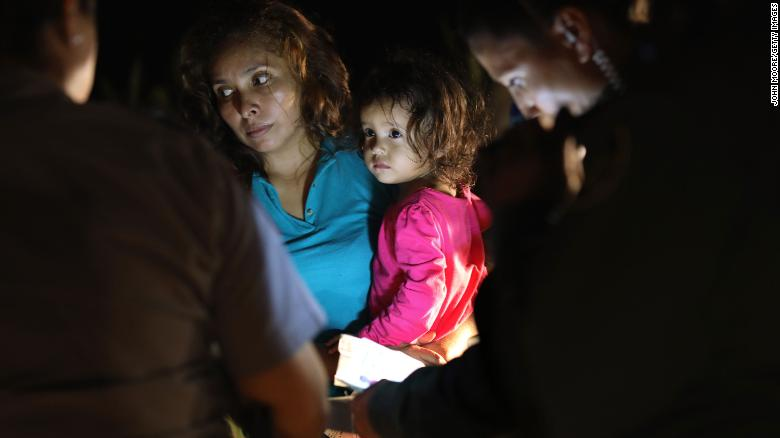 "MCALLEN, TX - JUNE 12:  A Honduran mother holds her two-year-old as U.S. Border Patrol as agents review their papers near the U.S.-Mexico border on June 12, 2018 in McAllen, Texas. The asylum seekers had rafted across the Rio Grande from Mexico and were detained by U.S. Border Patrol agents before being sent to a processing center for possible separation. Customs and Border Protection (CBP) is executing the Trump administration's ""zero tolerance"" policy towards undocumented immigrants. U.S. Attorney General Jeff Sessions also said that domestic and gang violence in immigrants' country of origin would no longer qualify them for political asylum status.  (Photo by John Moore/Getty Images)"
