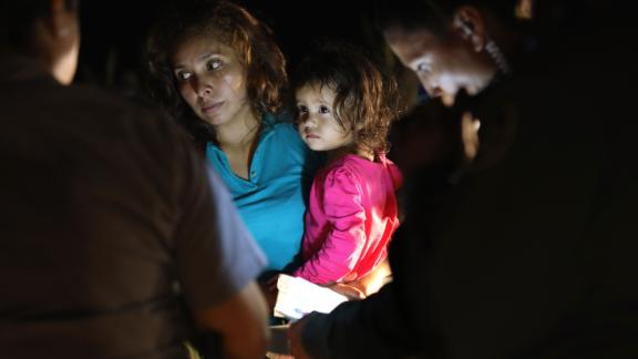 MCALLEN, TX - JUNE 12:  A Honduran mother holds her two-year-old as U.S. Border Patrol as agents review their papers near the U.S.-Mexico border on June 12, 2018 in McAllen, Texas. The asylum seekers had rafted across the Rio Grande from Mexico and were detained by U.S. Border Patrol agents before being sent to a processing center for possible separation. Customs and Border Protection (CBP) is executing the Trump administration