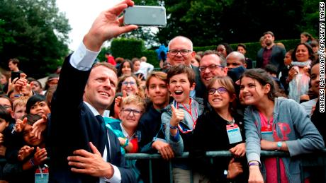 TOPSHOT - French President Emmanuel Macron (C) takes a 'selfie' with members of the crowd, as he leaves after a ceremony commemorating General Charles De Gaulle's June 1940 appeal for French resistance against Nazi Germany, at the Mont Valerien National Memorial in Suresnes on the outskirts of Paris on June 18, 2018. (Photo by CHARLES PLATIAU / POOL / AFP)        (Photo credit should read CHARLES PLATIAU/AFP/Getty Images)