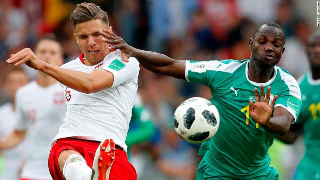 Poland's Jan Bednarek, left, clears the ball past Senegal's Moussa Konate on Tuesday. Senegal won the match 2-1.