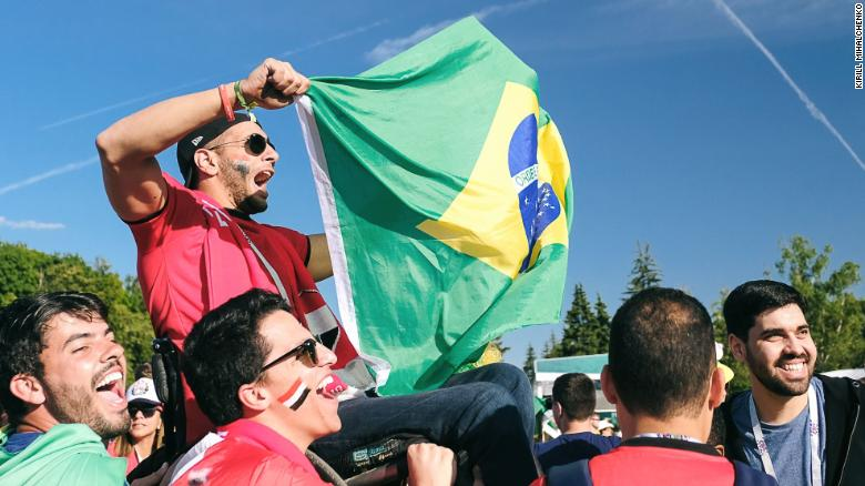 Hassan Sedky, 25, holds cheers on Brazil while football fans lift his wheelchair during World Cup opening festivities.