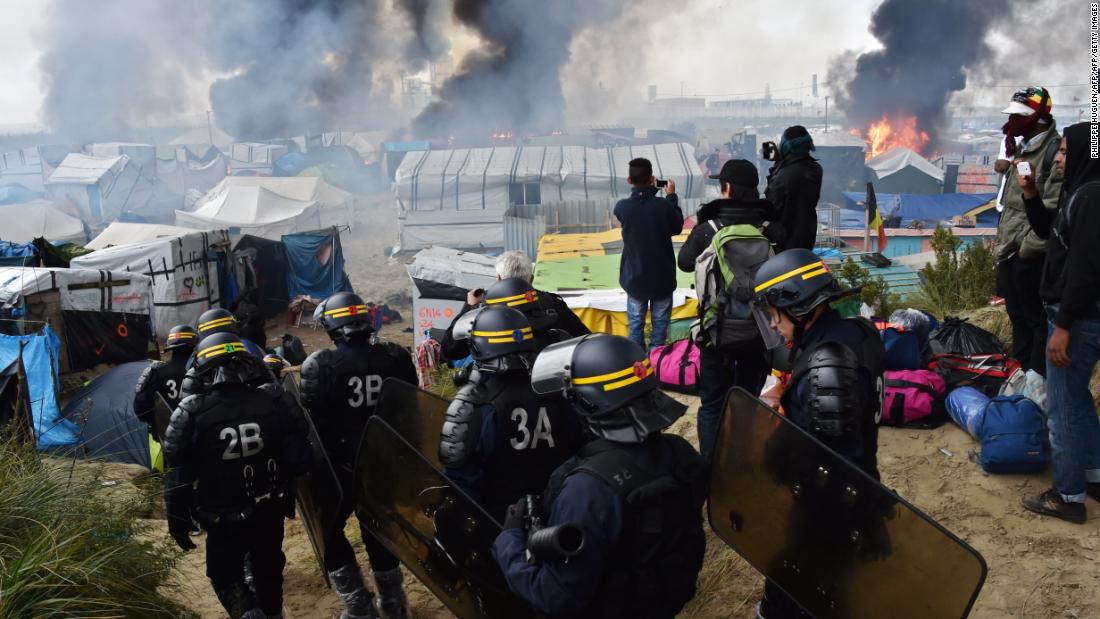 "French anti-riot police officers arrive in October 2016 to clear the Calais ""Jungle""."
