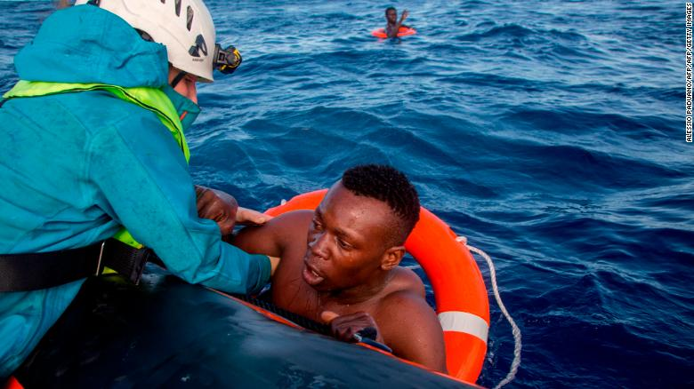 A member of German NGO Sea-Watch (L) helps a migrant to board a boat after he was recovered in the Mediterranean Sea on November 6, 2017. During a shipwreck, five people died, including a newborn child. According to the German NGO Sea-Watch, which has saved 58 migrants, the violent behavior of the Libyan coast guard caused the death of five persons.   / AFP PHOTO / Alessio Paduano        (Photo credit should read ALESSIO PADUANO/AFP/Getty Images)