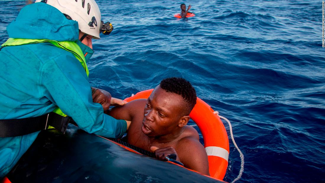 A member of Sea-Watch helps a migrant to board a boat after he was recovered in the Mediterranean on November 6, 2017. Five people died during the shipwreck.