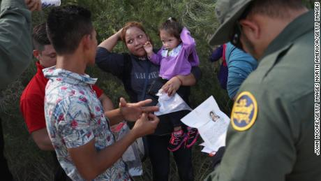 "MCALLEN, TX - JUNE 12:  U.S. Border Patrol agents ask a group of Central American asylum seekers to remove hair bands and weddding rings before taking them into custody on June 12, 2018 near McAllen, Texas. The immigrant families were then sent to a U.S. Customs and Border Protection (CBP) processing center for possible separation. U.S. border authorities are executing the Trump administration's ""zero tolerance"" policy towards undocumented immigrants. U.S. Attorney General Jeff Sessions also said that domestic and gang violence in immigrants' country of origin would no longer qualify them for political asylum status.  (Photo by John Moore/Getty Images)"