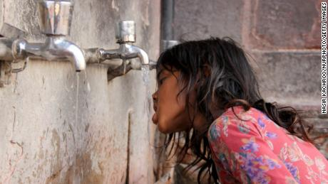 As Delhi Bolis,a girl can be seen quenching his thirst in Delhi, India, on 24 May 2018. Heat wave to continue across northern, central India for four days, temperatures likely to touch 45 degrees Celsius (Photo by Nasir Kachroo/NurPhoto via Getty Images)